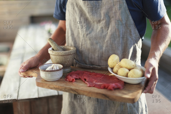 Man carrying cutting board with raw meat and potatoes