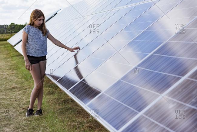 Girl standing next to solar panels