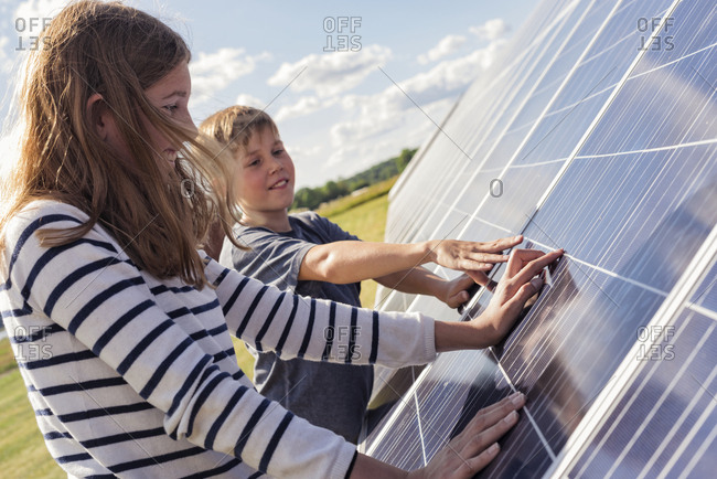 Boy and girl touching solar panels