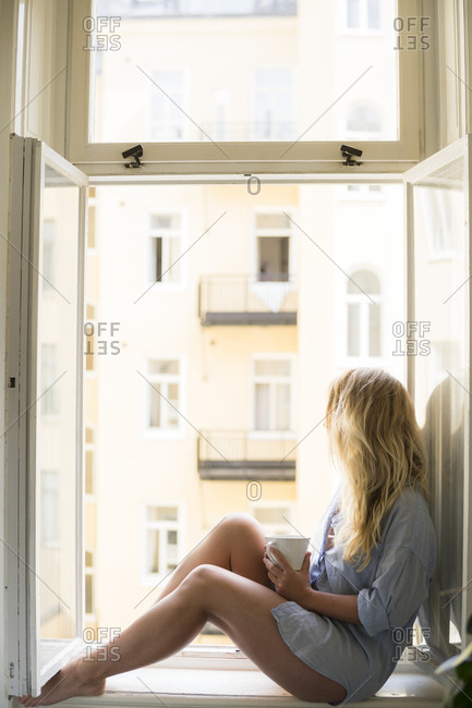 Woman drinking coffee on window still