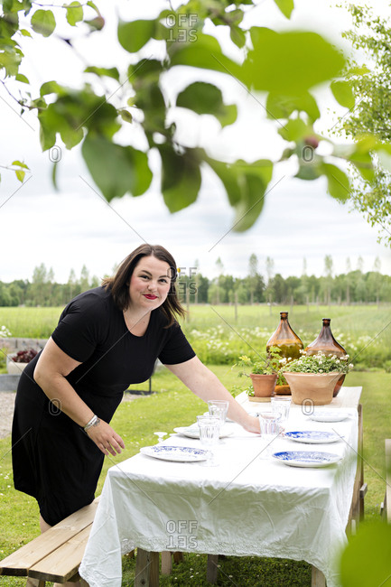 Woman preparing table outdoors
