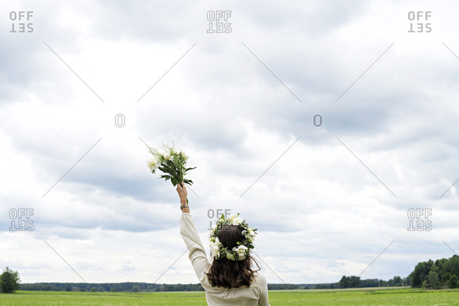 Woman wearing wreath standing in field