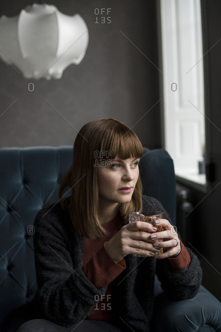Woman sitting with drink on sofa