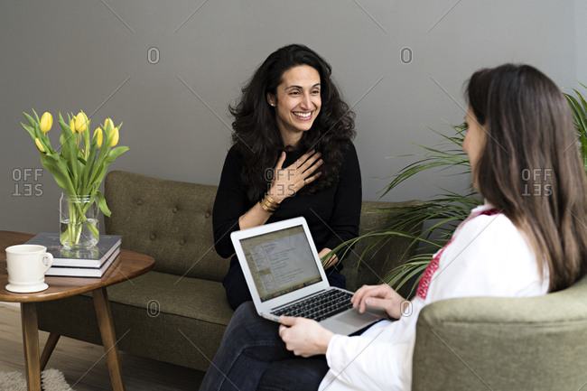 Female colleagues using laptop in office