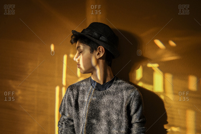 Boy wearing hat with eyes closed standing against yellow wall at home