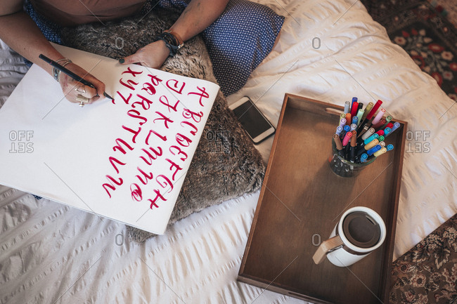 High angle view of artist doing calligraphy while sitting on bed at home