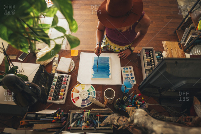 High angle view of artist painting on table while standing at home