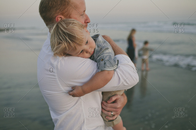Father carrying son while mother playing with boys on shore