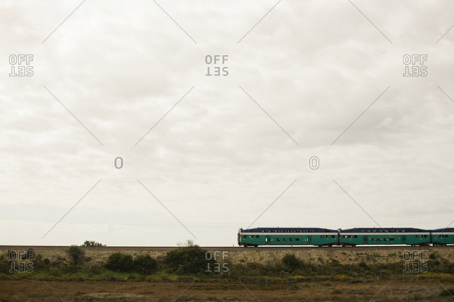 Train on railroad track against cloudy sky