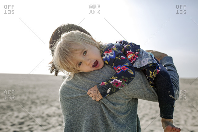 Portrait of cute daughter carried by her mother against sky at beach