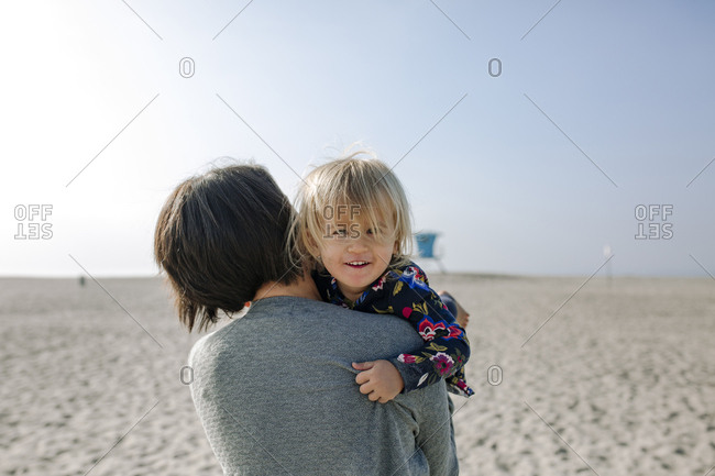 Portrait of daughter carried by her mother against sky at beach