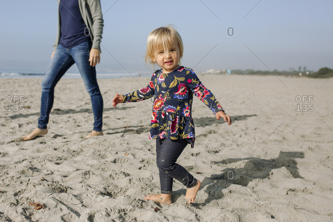 Portrait of cute daughter with mother walking at beach