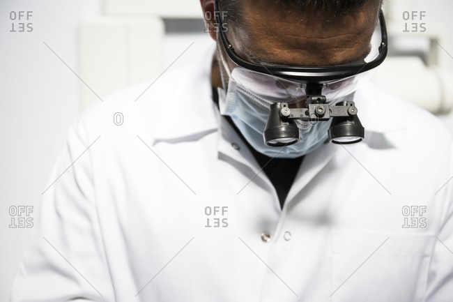 Close up of dentist wearing dental loupes while at work