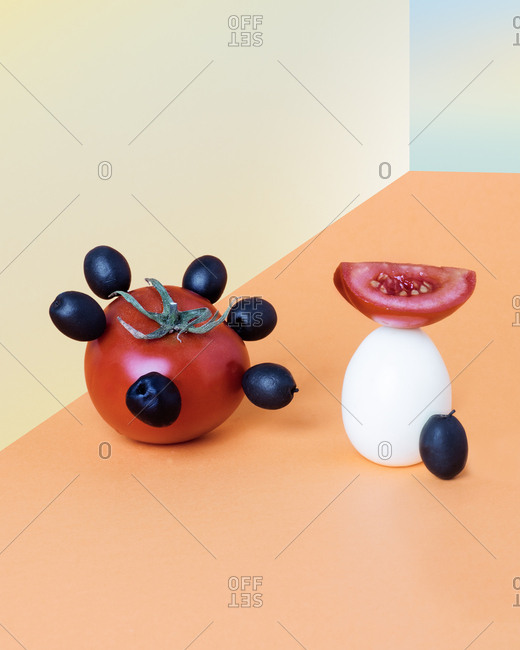 Surreal food presentation with tomatoes, olives, and an egg