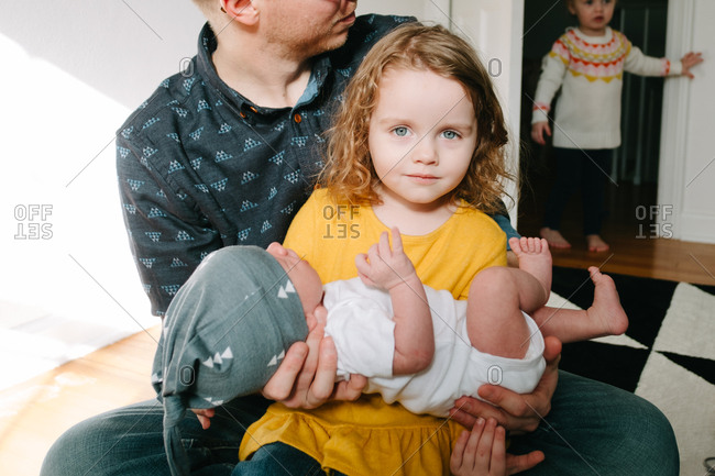 Little girl holding newborn sibling as dad gives a helping hand