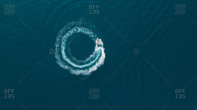 Aerial view of a boat driving in circle in the sea.