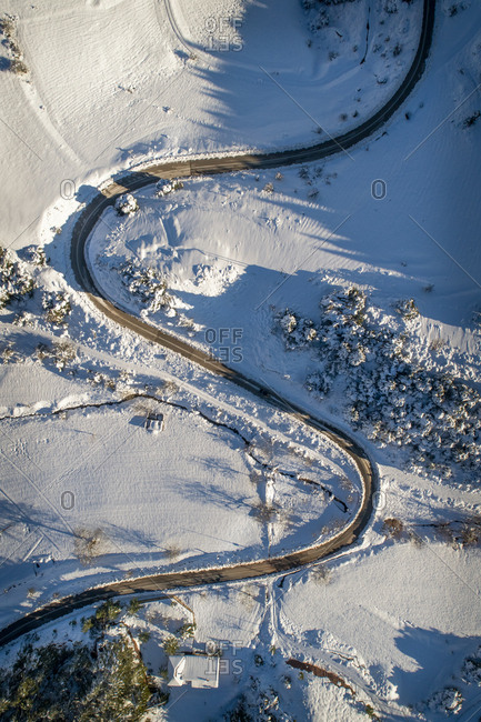 Aerial view of an empty zigzag road surrounded by snow.