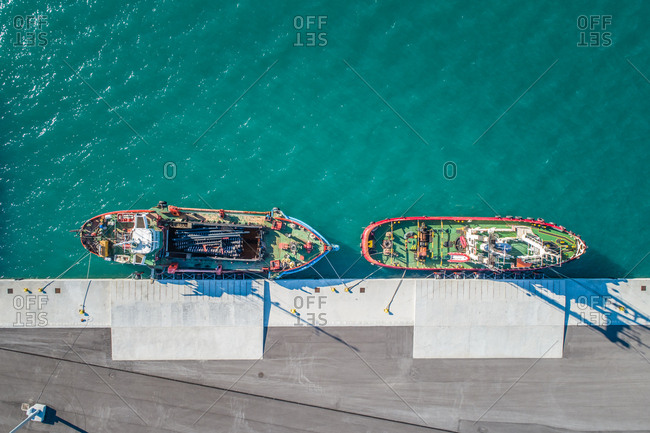 Aerial view of two fishing boats moored in harbour in greece.