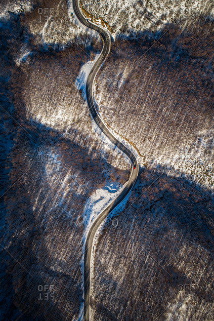 Aerial view of a zigzag road in the forest during winter.