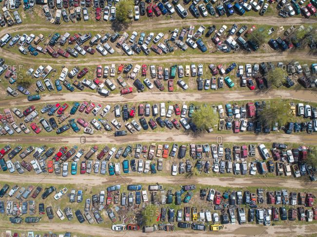 Aerial view of wrecked cars parked in a land fill scrapyard.