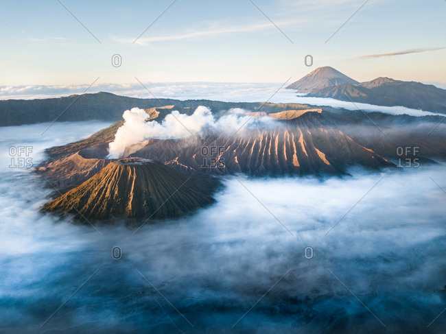 Aerial view of the active Volcano Bromo through clouds and smoke in Indonesia.