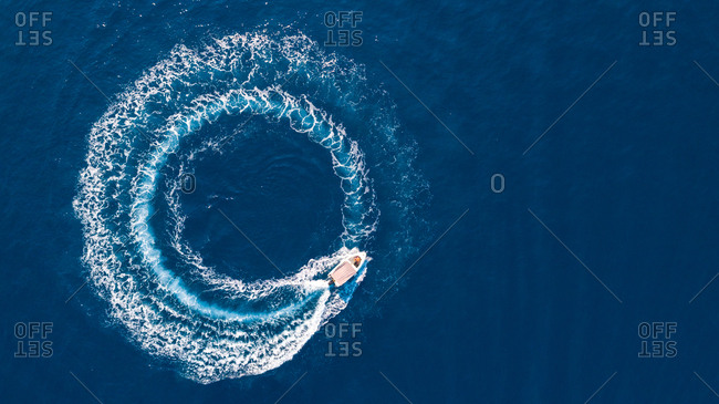Aerial photography of a boat creating circle with wake in the Ionan sea close to Ithaca island in Greece.
