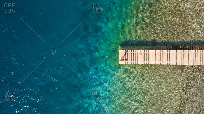 Aerial photography of a boy on a pontoon in the sea in Kiani Akti, Greece.