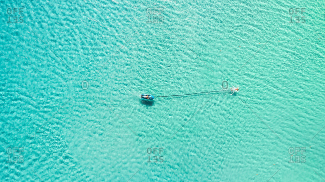 Aerial photography of people swimming in the clear blue sea of the greek island Andros.