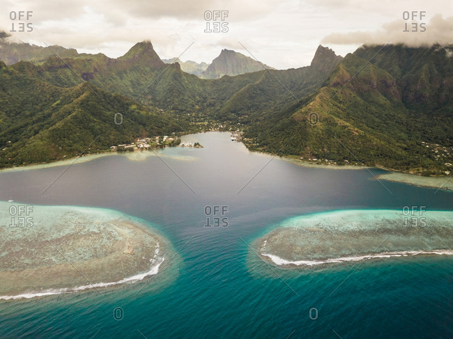 Aerial view of Moorea island and its shallow lagoon surrounded by the island's vertical mountains.