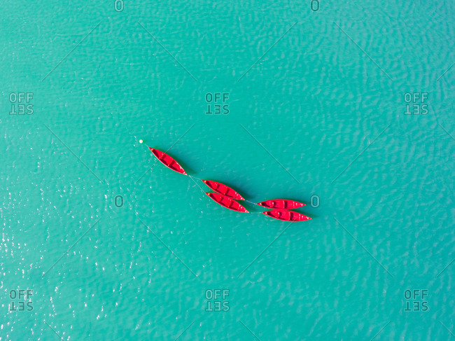 Aerial photography of empty red boats in the clear blue Lake Plastiras in Greece.