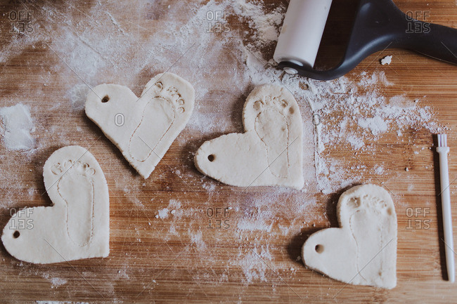 Overhead view of handmade plaster hearts with engravings of tiny feet