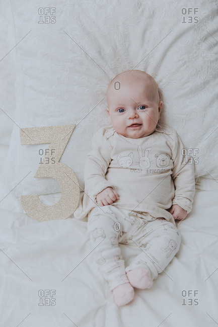 Portrait of baby girl lying next to cut out number three