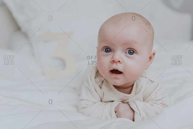 Portrait of baby girl lying on belly with cut out number three in background