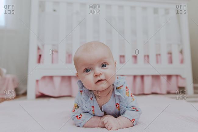 Portrait of happy baby girl on her belly in nursery