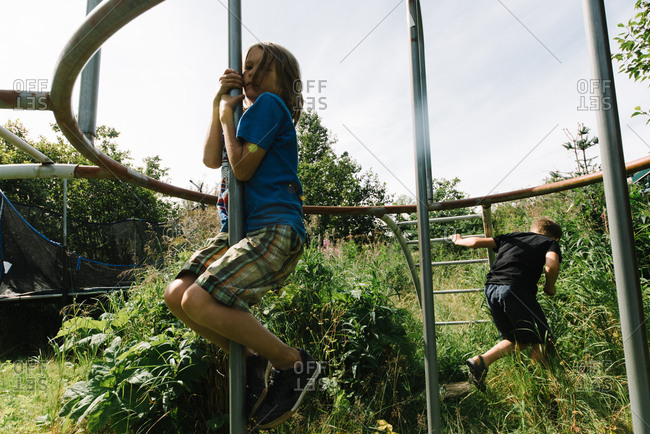 Boys playing on a climbing frame in an overgrown yard