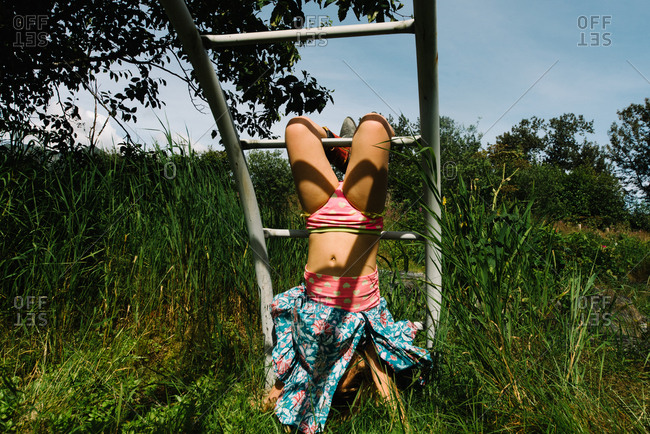 Young girl hanging upside down exposing underwear on climbing frame