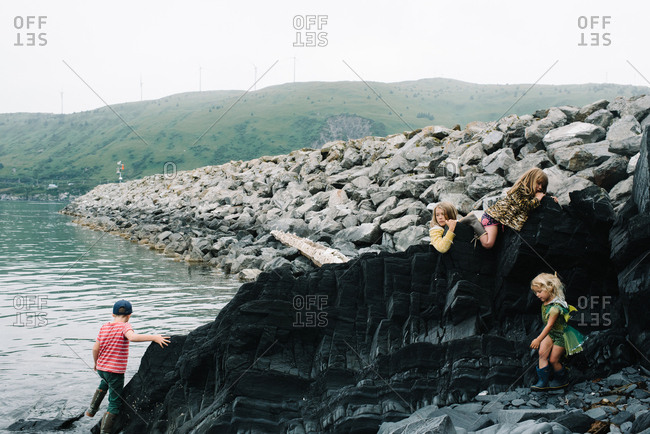 Group of kids exploring rock feature on shoreline of lake