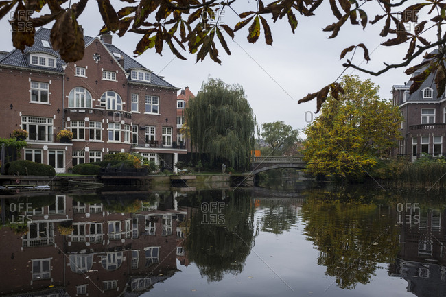 Amsterdam, Netherlands - October 30, 2016: Reflection of large home and trees in a canal next to Vondelpark