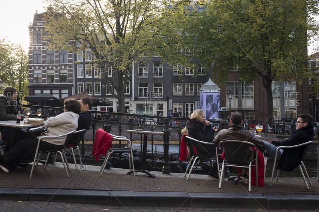 Amsterdam, Netherlands - October 30, 2016: People sitting outside enjoying a drink by an Amsterdam canal