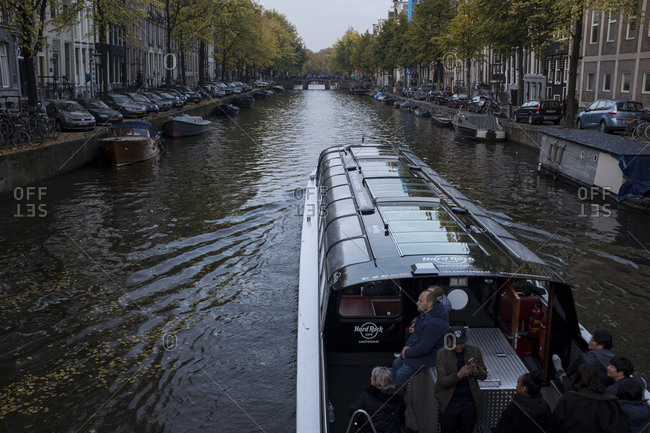 Amsterdam, Netherlands - October 30, 2016: Boat passing by an Amsterdam canal