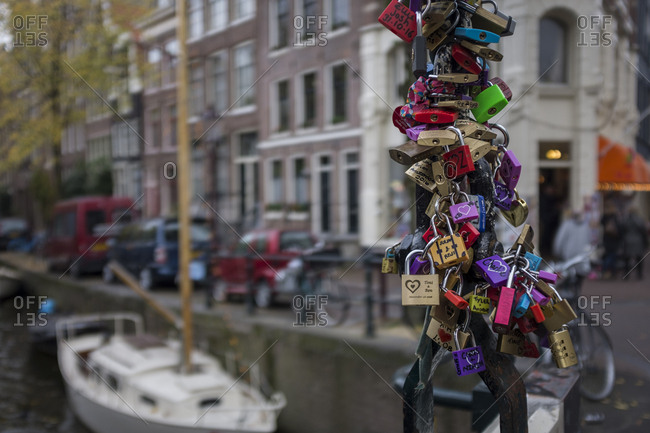 Amsterdam, Netherlands - November 1, 2016: Padlocks hanging on a bridge in Amsterdam