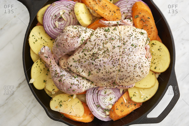 Raw ingredients for skillet roast whole chicken with vegetables ready to cook in iron skillet
