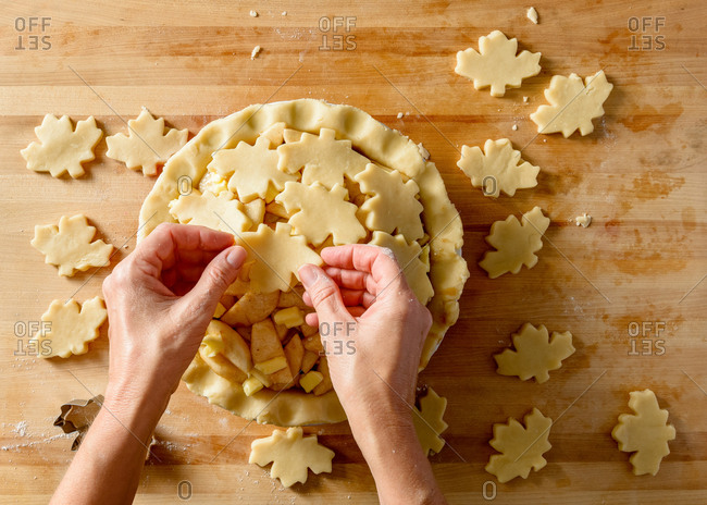 Arranging maple leaf shapes for apple pie crust