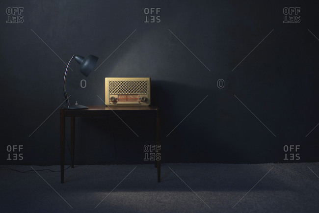 Vintage radio on wooden table lit by desk lamp