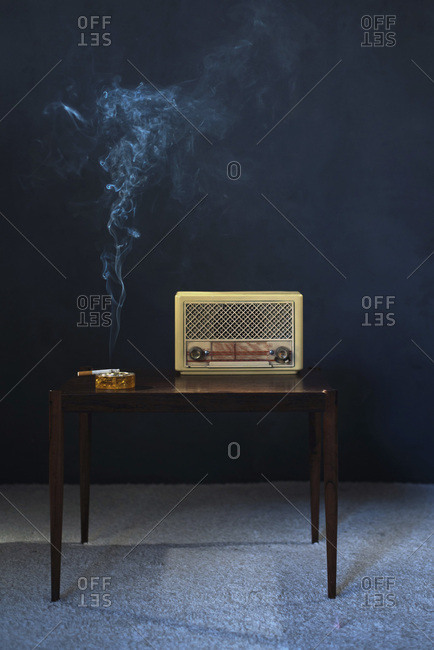 Ashtray with burning cigarette and transistor radio on vintage wooden table at night