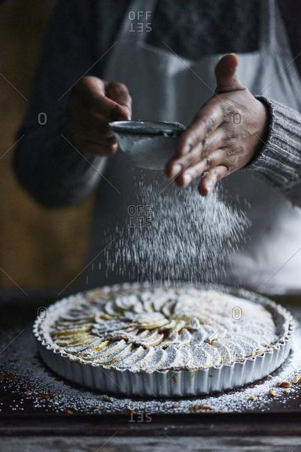 Baker dusting powdered sugar onto French apple tart