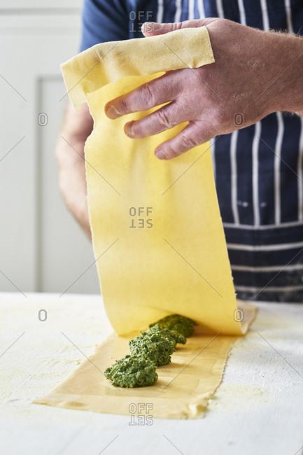 Chef using a sheet of fresh pasta to make homemade ravioli