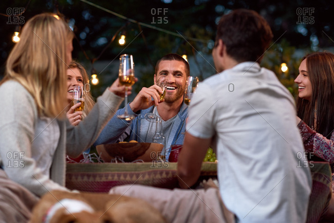 Friends having fun talking laughing drinking together at house party with garden lights