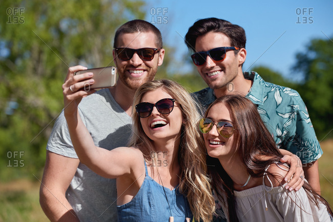 Happy attractive friends taking selfie with mobile cellphone healthy summer vacation vibes