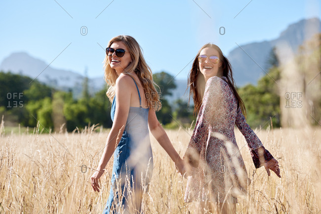 Beautiful girls holding hands in field walking towards summer music outdoor festival concert